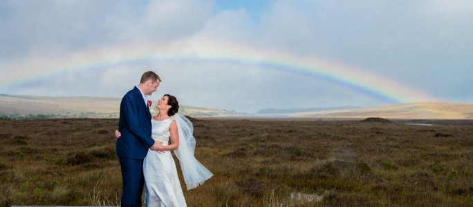 Bride & Groom with rainbow in the background. Barnesmore Gap