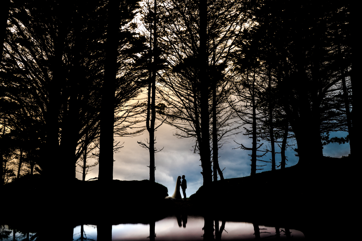 Long shot Silhouette of the bride and groom embracing in front of a lake and surrounded by trees. Photo by Paul McGinty of Ghorm Photography Studio.