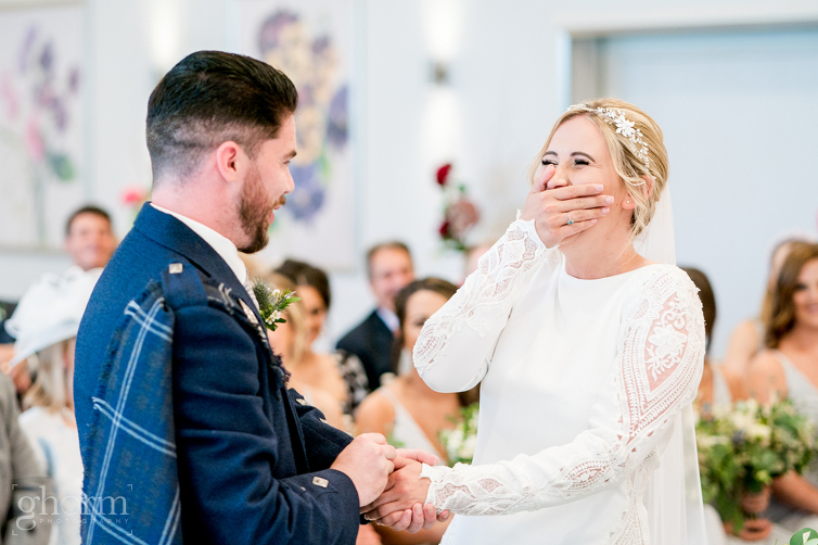 bride and groom having a laugh during their vows when the groom get his vows wrong and the bride bursts into laughter, Harveys Point hotel wedding on Lough eske, photo by Paul McGinty from Ghorm Studio Photography, www.ghormstudio.ie