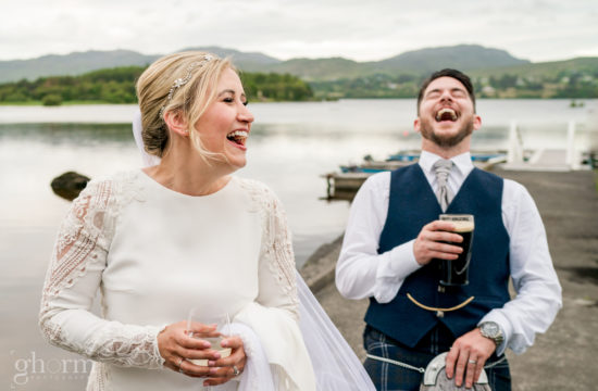 The bride and groom having a laugh during the photoshoot, one with a glass of wine and the groom with a pint of guinness, Harveys Point hotel wedding on Lough eske, photo by Paul McGinty from Ghorm Studio Photography, www.ghormstudio.ie