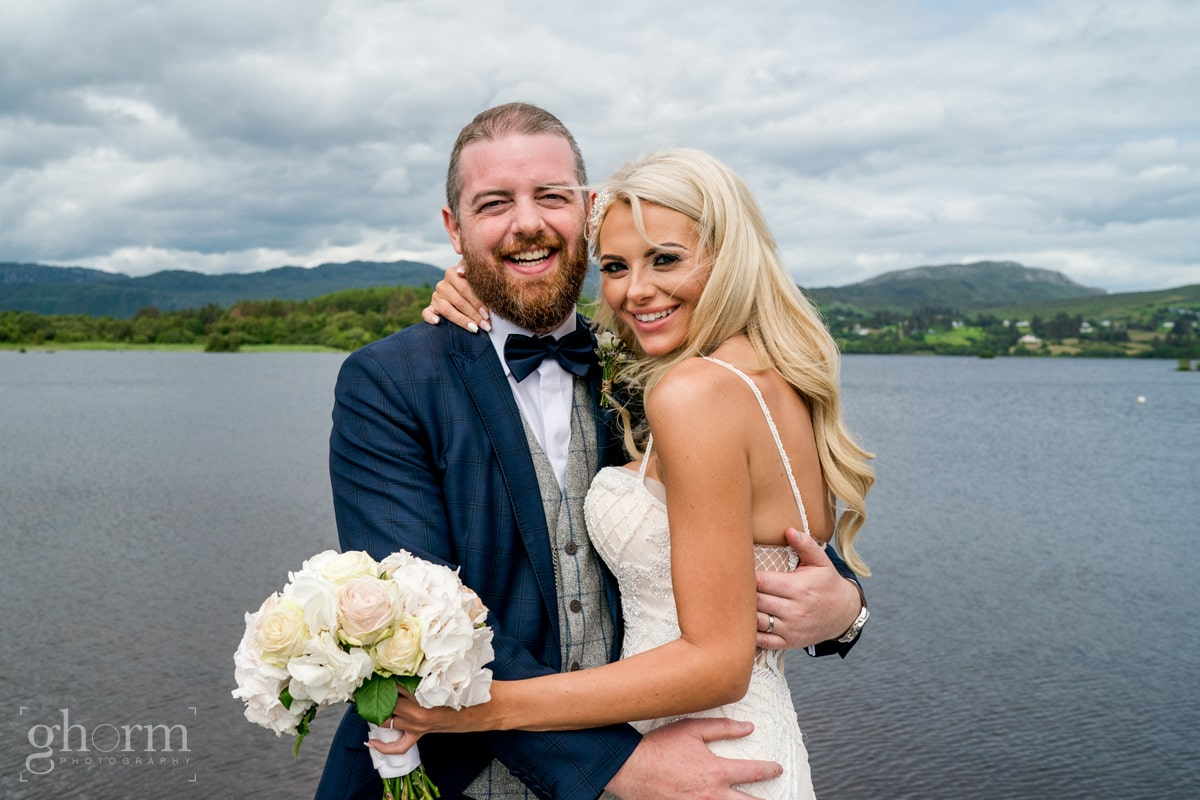 Bride and groom on the shores of lough eske with harveys Point in the background, photo by paul McGinty from Ghorm Studio Photography., having a cuddle