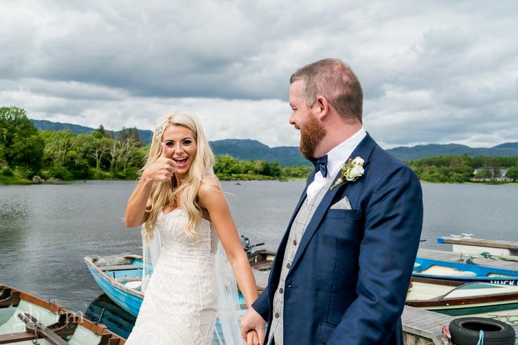 Bride and groom on the shores of lough eske with harveys Point in the background, photo by paul McGinty from Ghorm Studio Photography. walking hand in hand