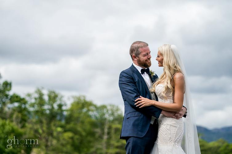Bride and groom on the shores of lough eske with harveys Point in the background, photo by paul McGinty from Ghorm Studio Photography.