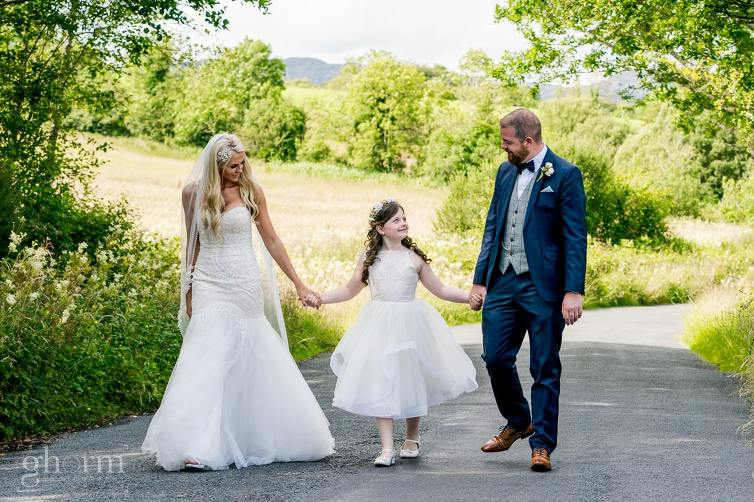 bride, groom and their daughter walking along the shore of Lough Eske, harveys Point, photo by paul McGinty from Ghorm Studio Photography.