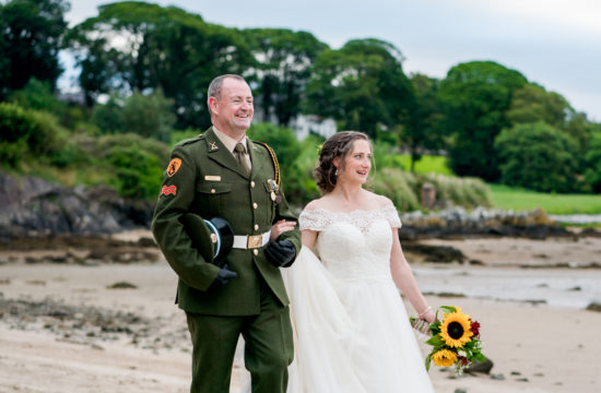 bride and groom dressed in his army uniform walking down a beach near Drumhalla house, Rathmullan , co donegal on their wedding day as the sun was starting to set. Photo by Paul McGinty from Ghorm Studio Photography.