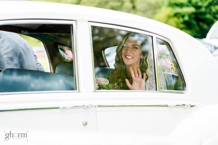 Bride waving out of her vintage car on the way to church, Mill park hotel wedding, Donegal Town, Photos by Paul McGinty from Ghorm Studio Photography