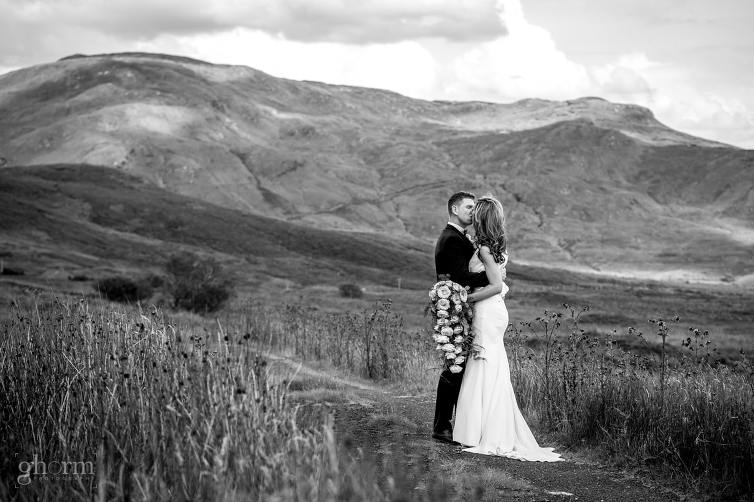 a black and white photos of a bride and groom kissing in the middle of the Bluestack mountains , Co Donegal, Ireland, Mill park hotel wedding, Donegal Town, Photos by Paul McGinty from Ghorm Studio Photography