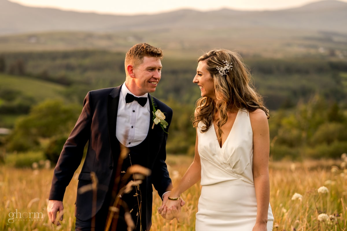 Bride and groom walking through meadow at sunset, Mill park hotel wedding, Donegal Town, Photos by Paul McGinty from Ghorm Studio Photography