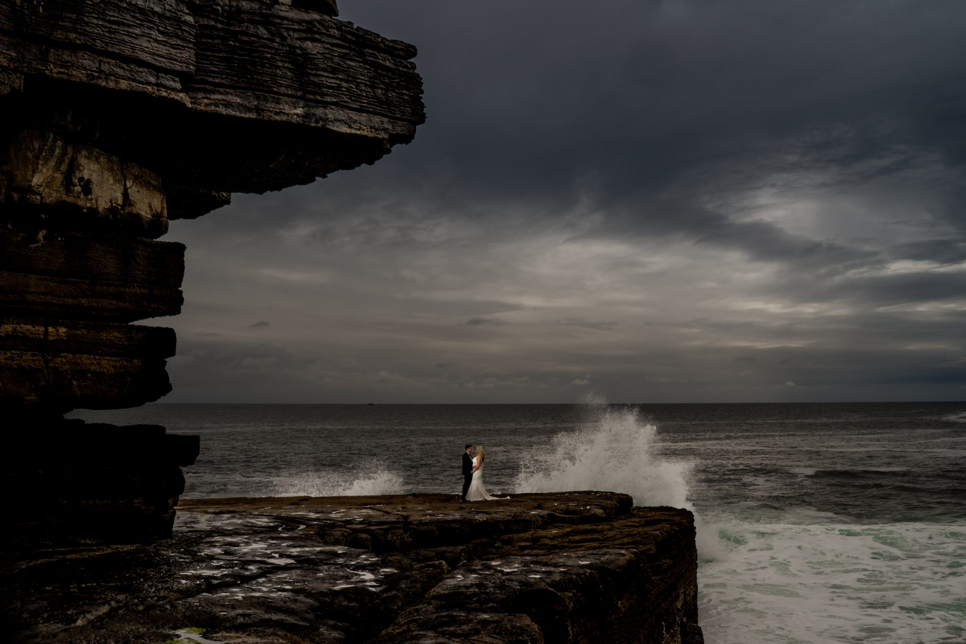 bride and groom at Muckross Head as a huge wave splashes behind them. on the wild atlantic way, Donegal, Photo by Paul McGinty from Ghorm Studio Photography.