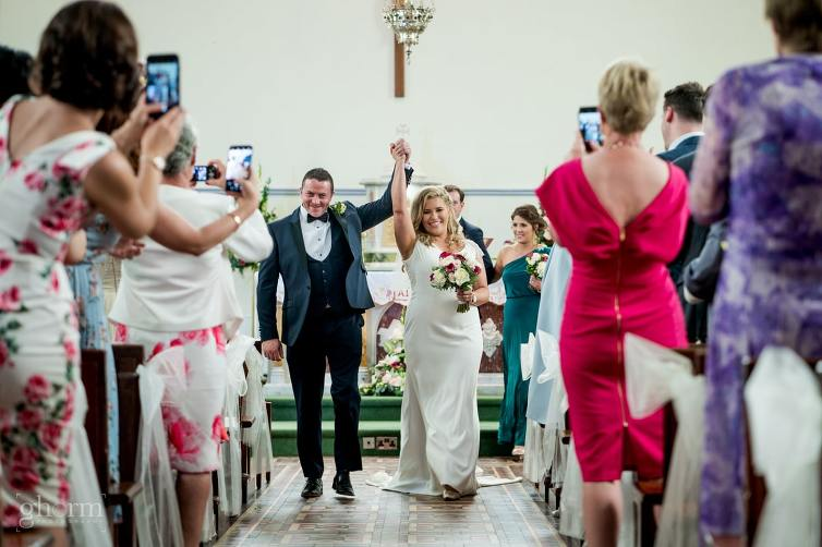 bride and groom walking down the aisle in Ballintra church, Bride and groom on their wedding day in the Villa Rose hotel Ballybofey, Co Donegal, Ireland. Photo by Paul McGinty from Ghorm Studio Photography
