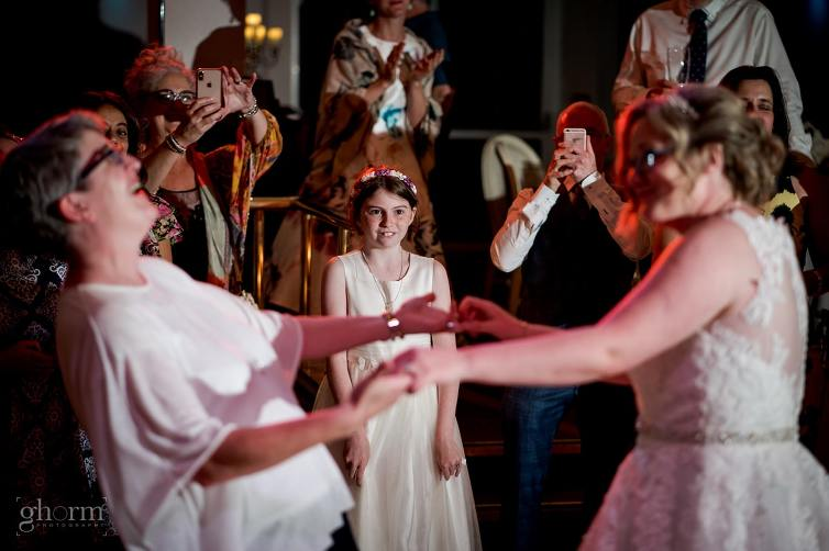 same sex first dance as flower girls looks on.