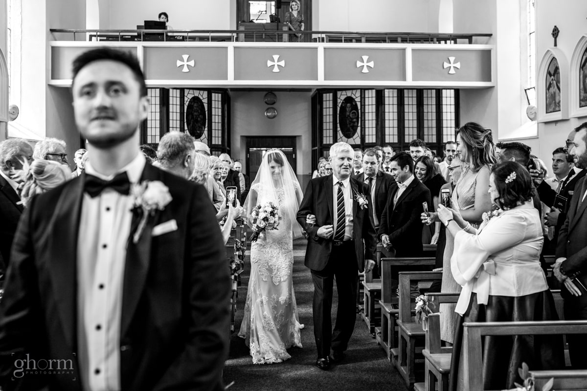 bride walking down the aisle with her father as the groom waits, Lough Eske Castle wedding, Photos by Paul McGinty from Ghorm Studio Photography