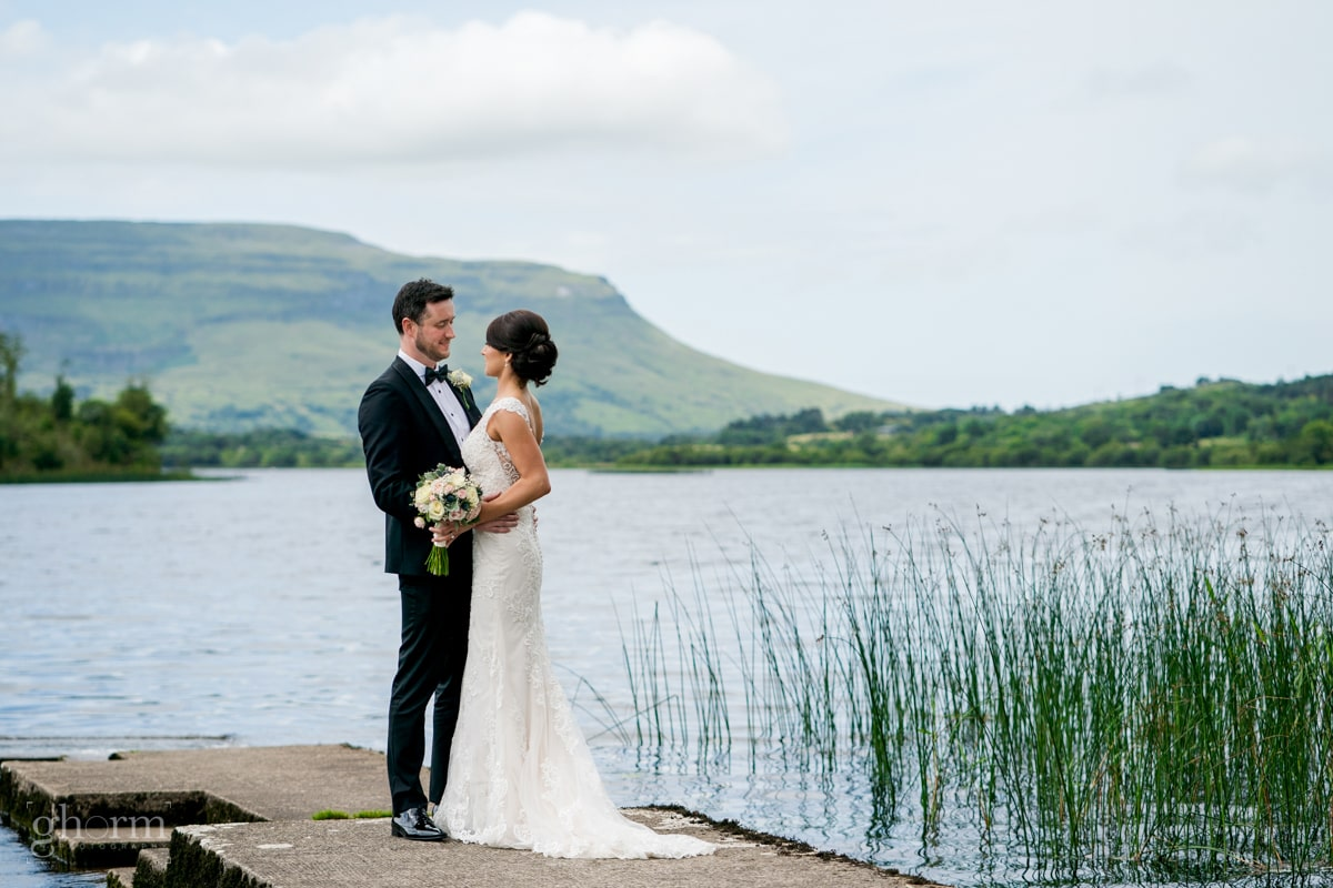 bride and groom on a jetty on a lake in county leitrim with the eagles rock in the background. Lough Eske Castle wedding, Photos by Paul McGinty from Ghorm Studio Photography