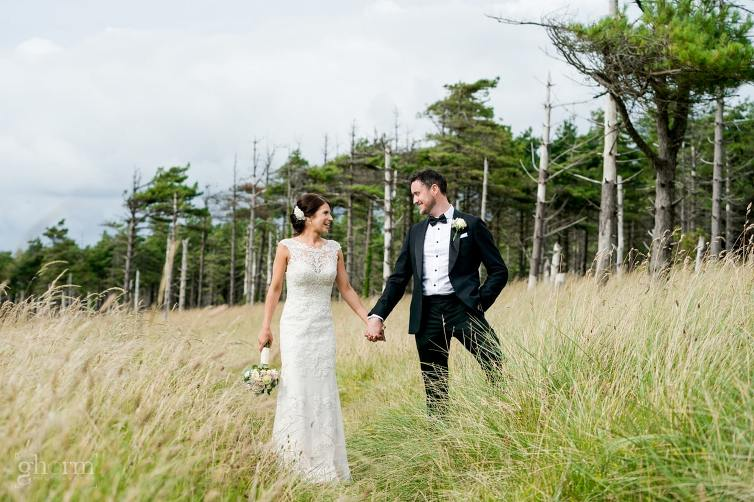 bride and groom in front of trees, groom in a tux and the bride in a long white wedding dress. Lough Eske Castle wedding, Photos by Paul McGinty from Ghorm Studio Photography