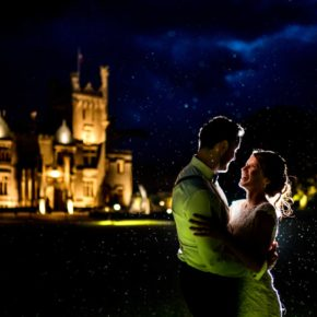 bride and groom in the rain in front of the castle as the sun sets, Lough Eske Castle wedding, Photos by Paul McGinty from Ghorm Studio Photography
