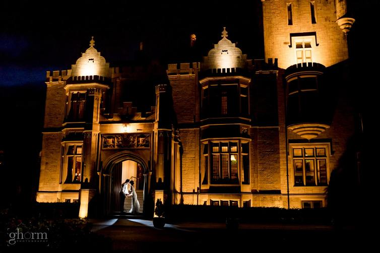 bride and groom in the doorway of Lough Eske castle at nighttime, Lough Eske Castle wedding, Photos by Paul McGinty from Ghorm Studio Photography