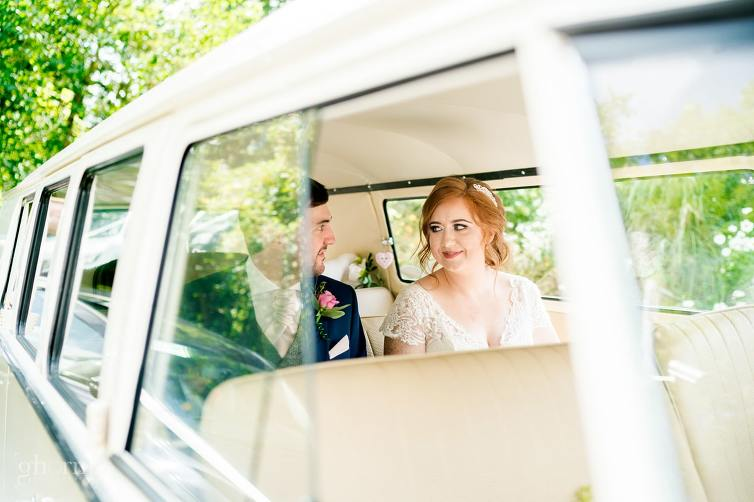 bride and groom in a vintage vw camper bus,