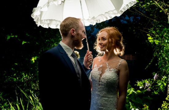 bride and groom under a umbrella out the Mill Park hotel, Donegal Town as the rain pours down. Photo by Paul McGinty from Ghorm Studio Photography