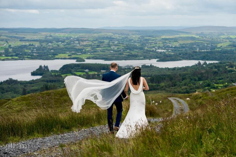bride and groom walking through the blue stack mountains, co donegal as her view blows in the wind, Claire and Lachlan