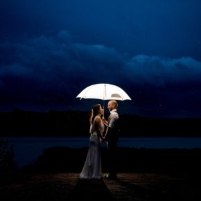 bride and groom standing under an umbrella as the rain pours down, Claire and Lachlan's wedding day in the best wedding venue in donegal, Harvey''s Point on the shore of Lough Eske. Photo by Paul McGinty from Ghorm Studio Photography