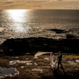 Bride and groom walking along the sea cliffs in Donegal as the sun sets. Photo by Paul McGinty from Ghorm Studio Photography, Lough Eske, Donegal Town. Dearbhla and Michael got married in St Marys Church Killybegs with the reception afterwards in Lough Eske Castle, Co Donegal.