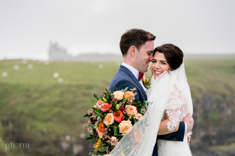 groom hugging the bride as the rain came in on the cliffs at Mullaghmore, co sligo. Markree Castle wedding photographer, Photo by Paul McGinty , Ghorm Studio Photography