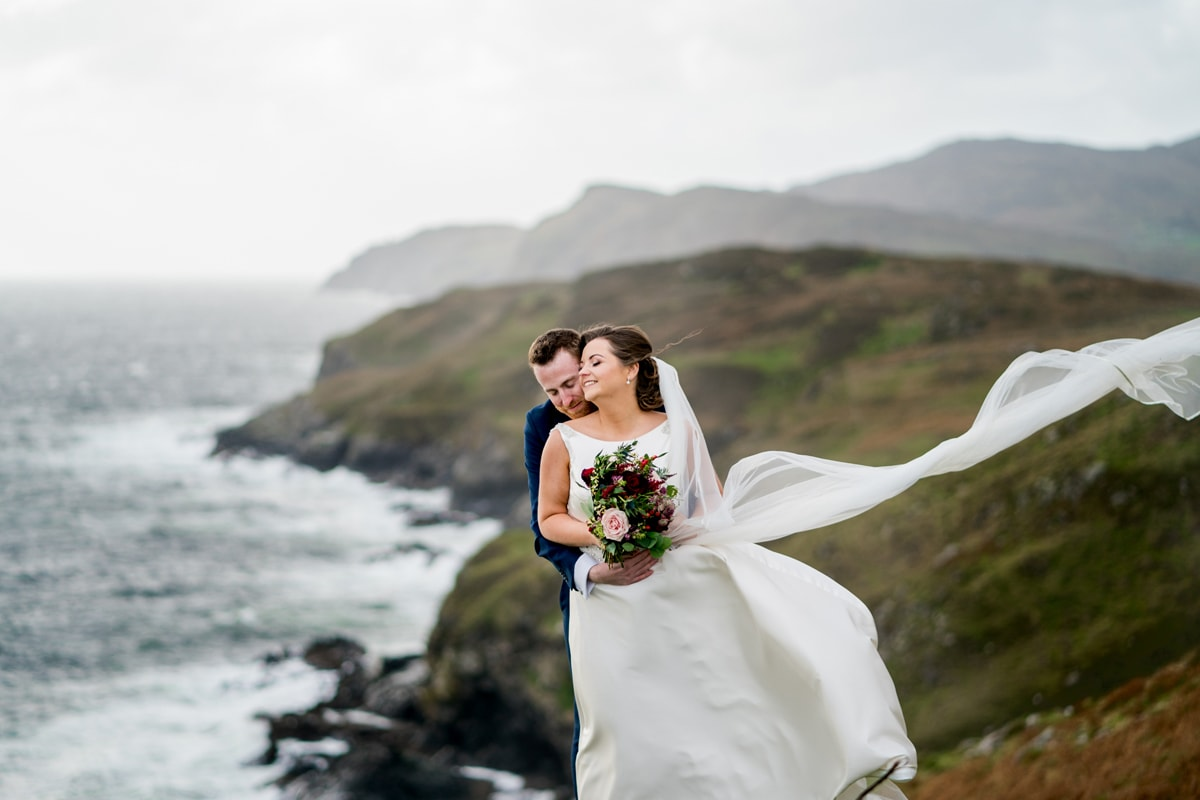 Groom holding the bride as a storm hits Ireland. The couple are on the cliffs at Muckross Head, Kilcar, Co Donegal with Sliabh Liag in the background. Photo by Paul McGinty from Ghorm Studio Photography