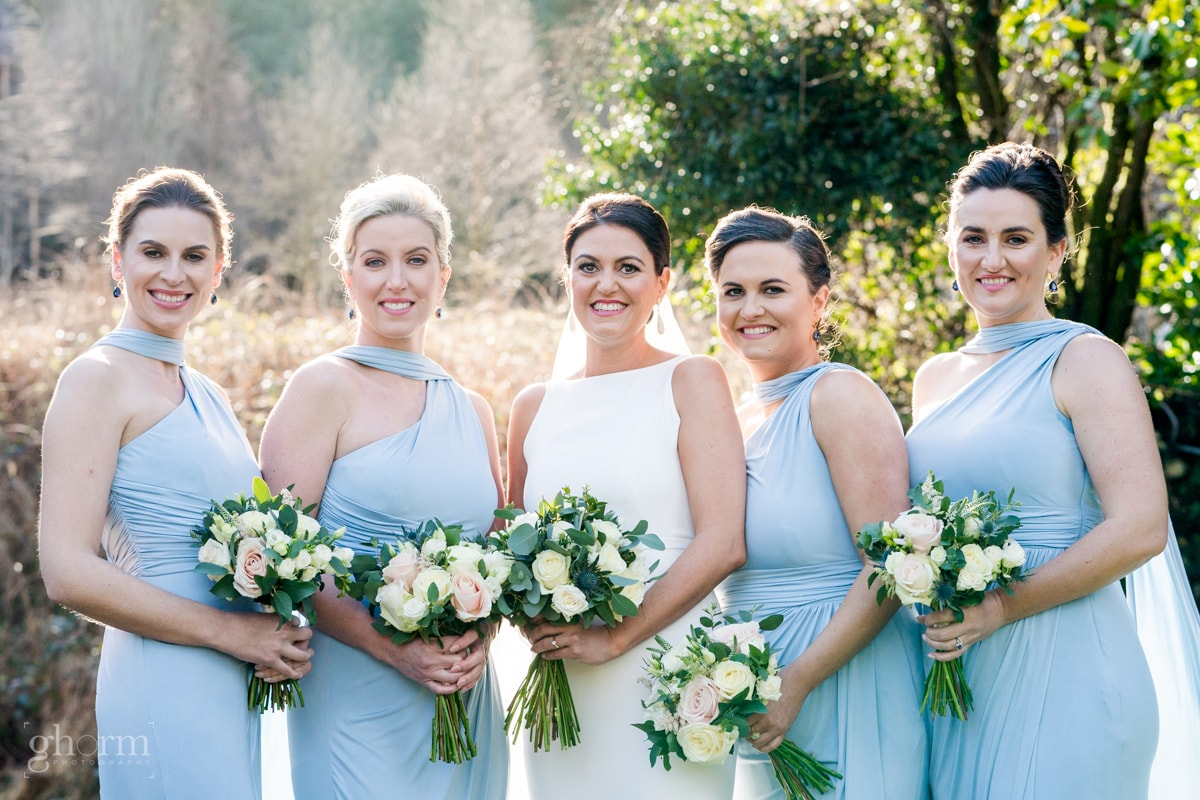 Bride in her full length white dress with her bridesmaids in a light blue dress with their bouquets