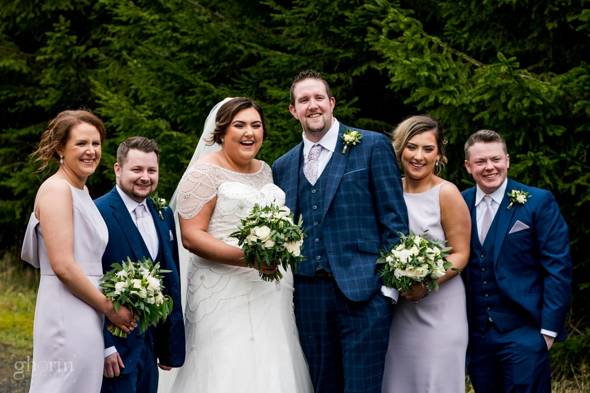 Bridal party, groomsmen in navy sits and bridesmaids in purple dress in a forest in Cavan, Ireland. Errigal Country House wedding, natural wedding photographer Donegal, Cavan, Sligo and leitrim, Paul McGinty from Ghorm Studio Photography based at Lough Eske, Donegal Town.