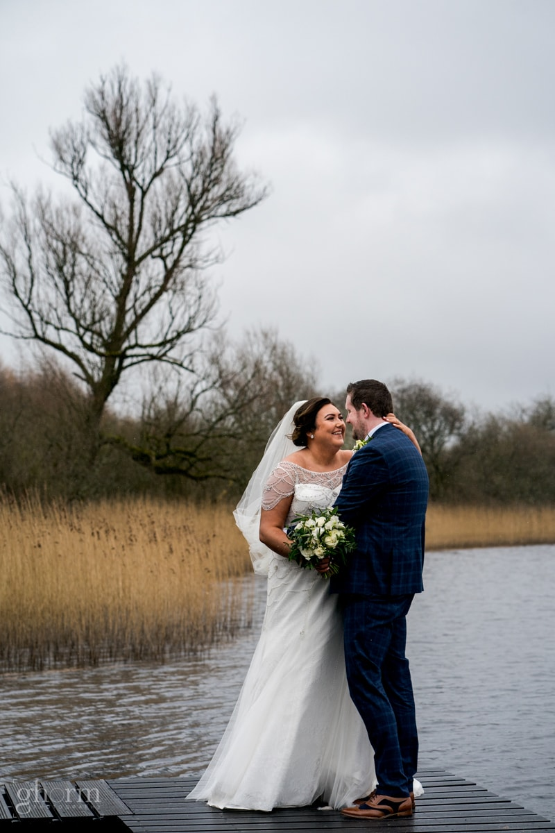 Bride in her full length white wedding dress on a jetty on a lake in Cavan with her newly wed groom. Errigal Country House wedding, natural wedding photographer Donegal, Cavan, Sligo and leitrim, Paul McGinty from Ghorm Studio Photography based at Lough Eske, Donegal Town.