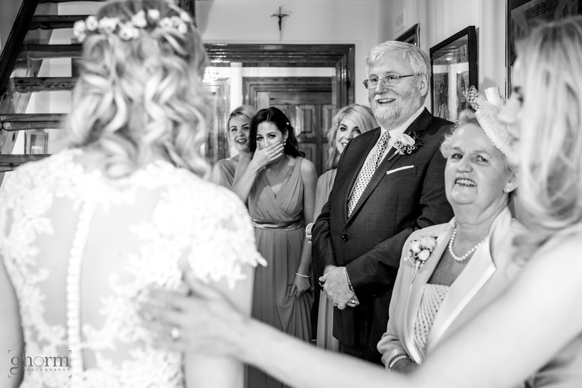 Black and white photo of a bride coming down the stair so her mother and father can see her for the first time in her dress. Photo By Paul McGinty from Ghorm studio Photography.