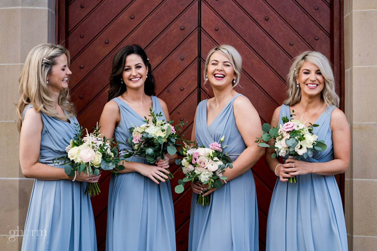 Bridesmaids in light blue full length dress  at the doors of the church in Letterkenny, Photo by Paul McGinty from Ghorm Studio Photography