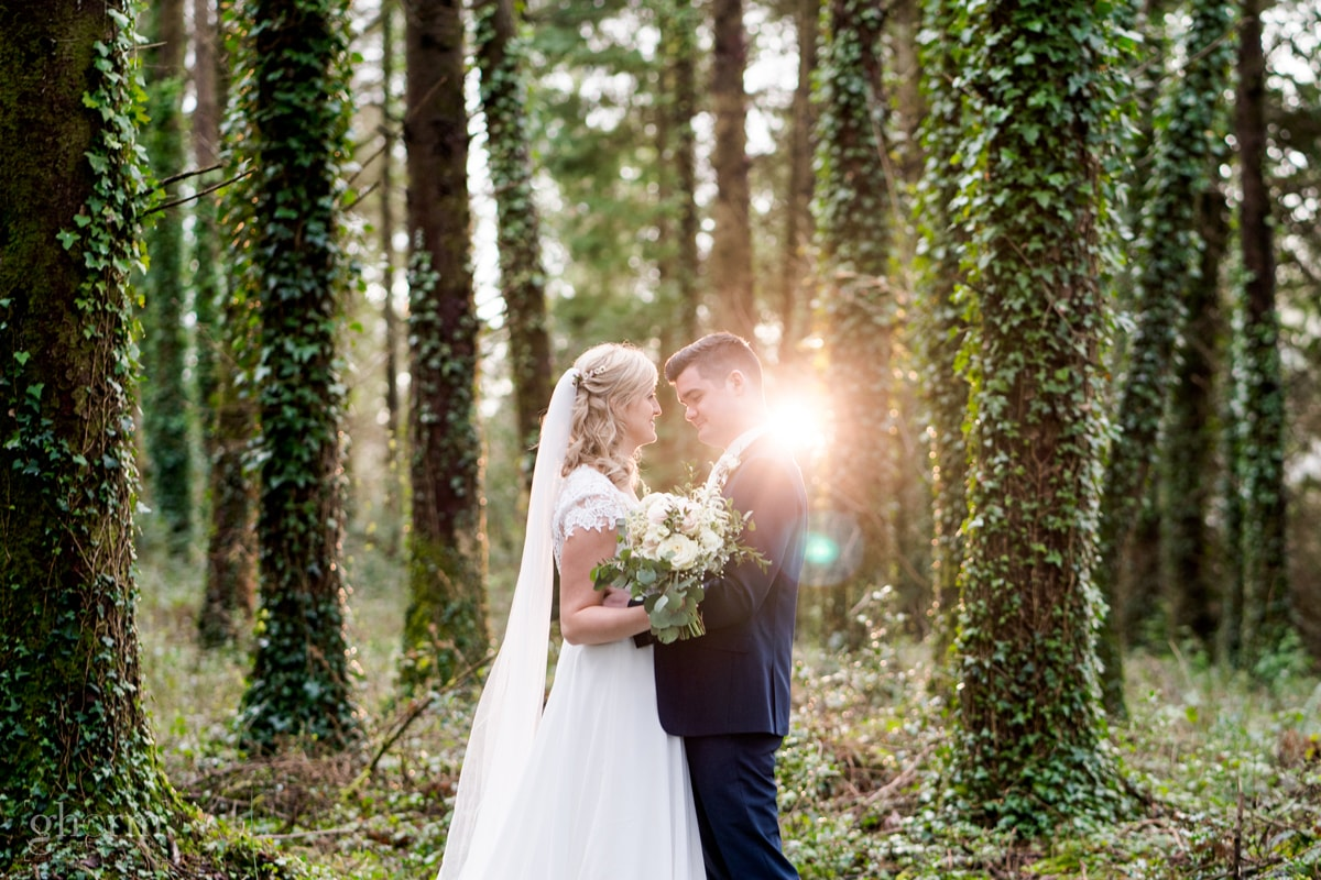 Bride and groom in a forest near Lough Eske, Donegal Town on their way to harvey's Point hotel as the sun sets through the trees. Photo by Paul McGinty from Ghorm Studio Photography.