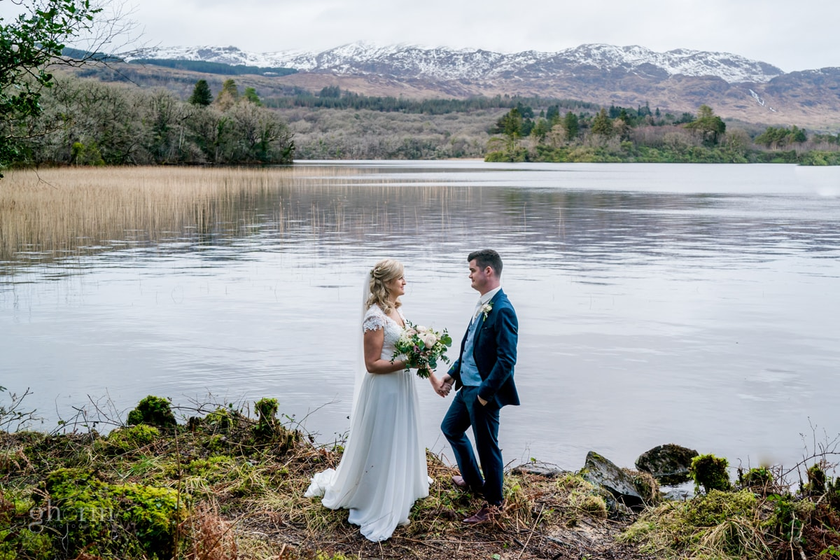 Bride looking at the groom on the shores of Lough Eske with snow capped Bluestack mountains in the background. Photo by Paul McGinty from Ghorm Studio Photography.