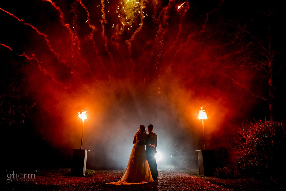 bride and groom on the pier at Harvey's Point, Lough Eske, Donegal Town, Ireland with a fireworks display at night before their first dance. Photo by Paul McGinty from Ghorm Studio Photography