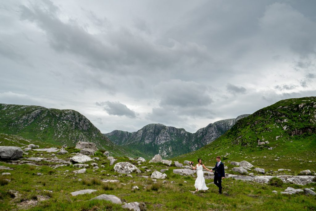 Bride and groom walking hand and hand through the Poisoned Glen, Co Donegal. The bride is wearing a beautiful white wedding dress and the groom is in a navy suit. Photography by Paul McGinty, Ghorm Studio Photography