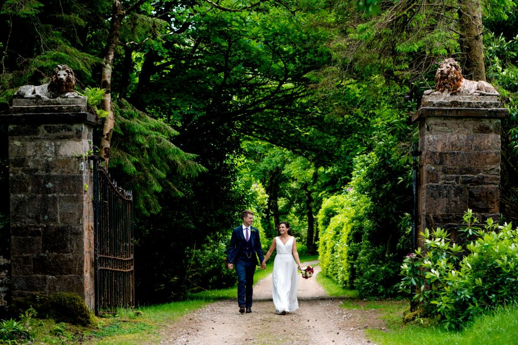 Bride in the white wedding dress, bouquet and groom in a blue suit and floral tie walking through McGuinness estate, Co Donegal. Photography by Paul McGinty, Ghorm Studio Photography