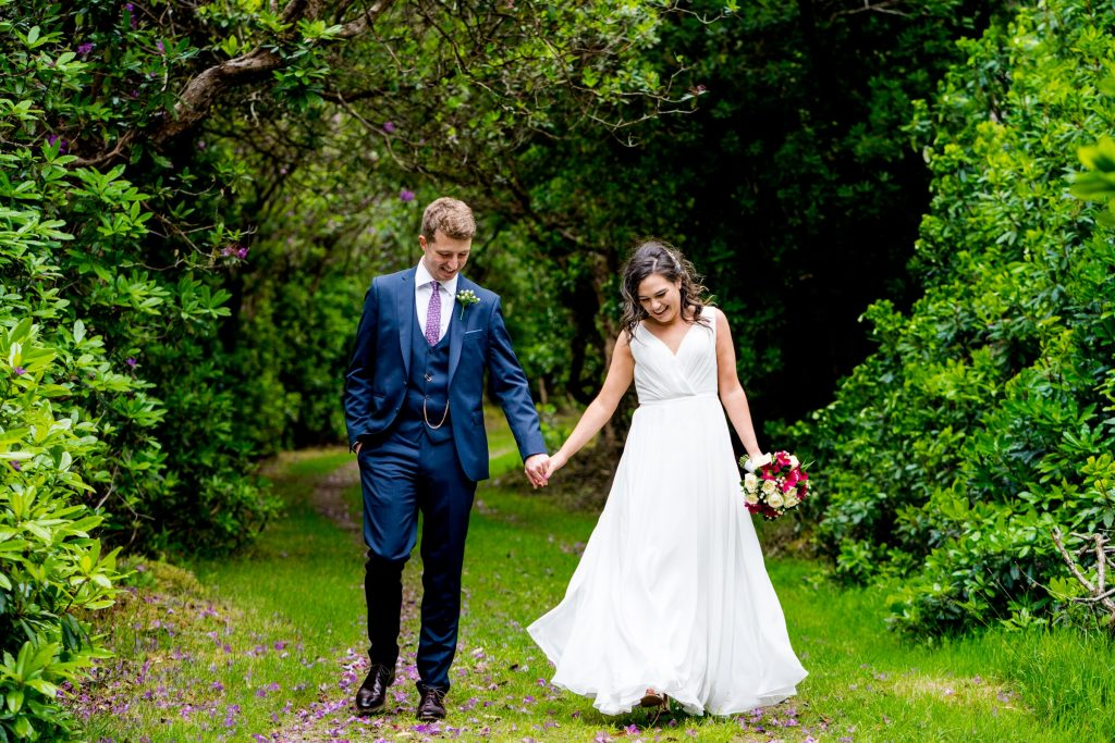 Bride and groom walking hand in hand through a forest of rhododendrons the Poisoned Glen, Co Donegal, Ireland. Photography by Paul McGinty, Ghorm Studio Photography