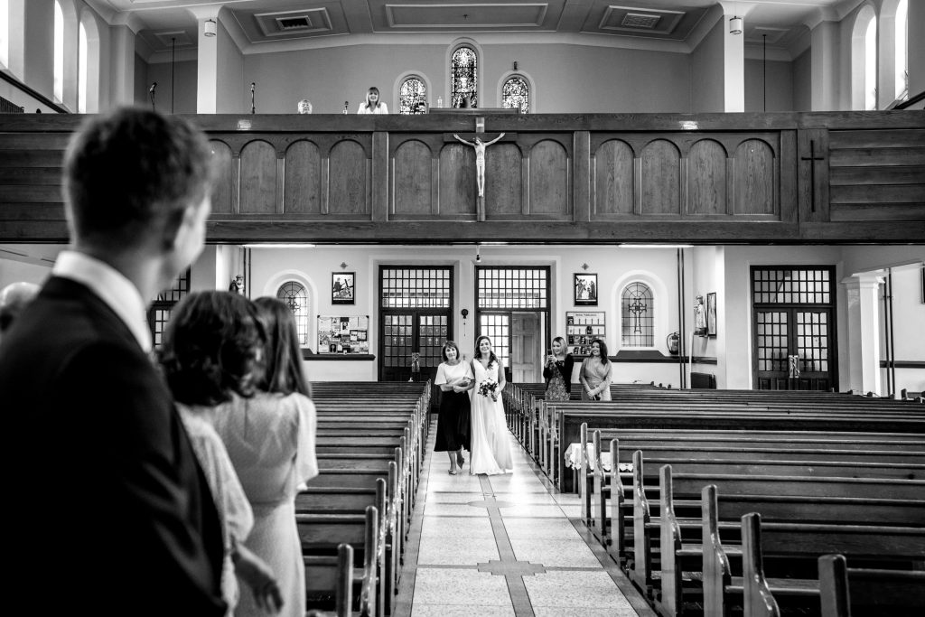 Bride walking up the aisle by her mother as her groom to be waits at the top of the alter. Photography by Paul McGinty, Ghorm Studio Photography