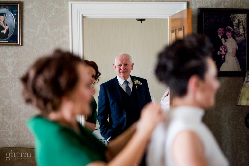 brides father looking at his daughter as the bide gets into her dress, bride and groom in donegal best wedding venue, harvey's point hotel on the shore of Lough Eske, Ghorm Studio Photography, donegal, sligo and leitrim wedding photographer