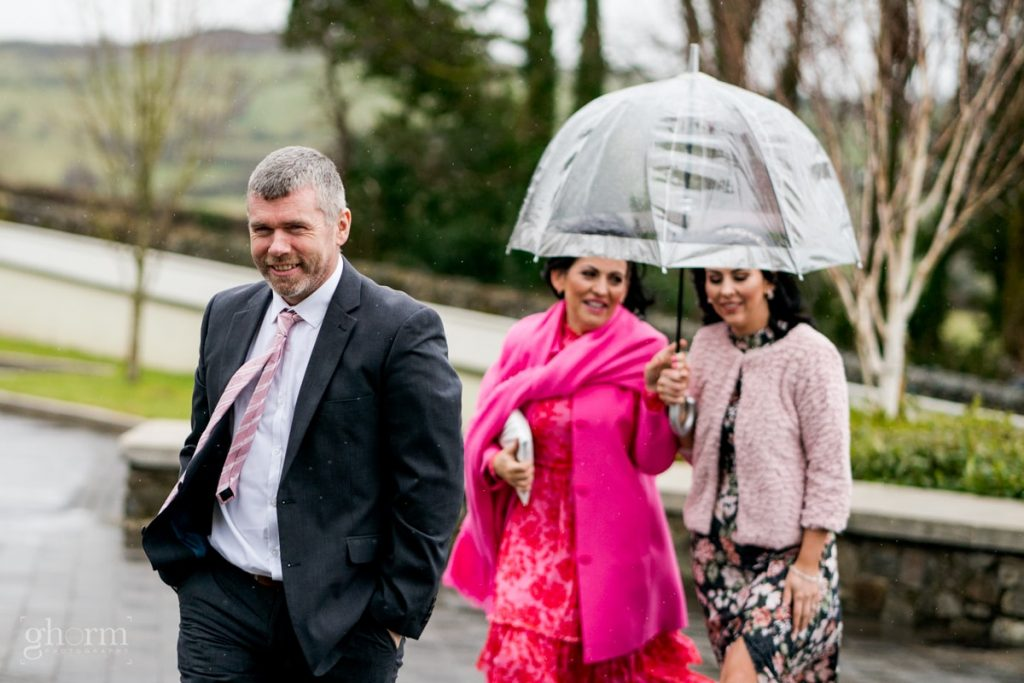 guests arriving with umbrellas, bride and groom in donegal best wedding venue, harvey's point hotel on the shore of Lough Eske, Ghorm Studio Photography, donegal, sligo and leitrim wedding photographer