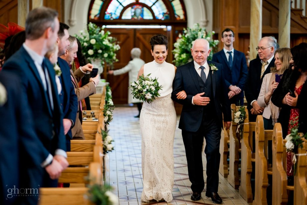 the bride being walked up the aisle by her father, bride and groom in donegal best wedding venue, harvey's point hotel on the shore of Lough Eske, Ghorm Studio Photography, donegal, sligo and leitrim wedding photographer