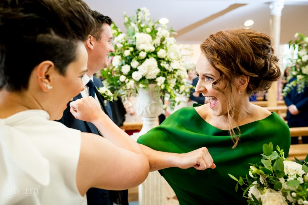 the bridesmaid elbow bumping the bride, bride and groom in donegal best wedding venue, harvey's point hotel on the shore of Lough Eske, Ghorm Studio Photography, donegal, sligo and leitrim wedding photographer