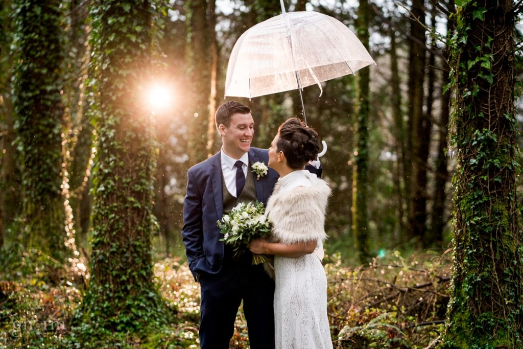 bride and groom in a forest under an umbrella as its raining, bride and groom in donegal best wedding venue, harvey's point hotel on the shore of Lough Eske, Ghorm Studio Photography, donegal, sligo and leitrim wedding photographer
