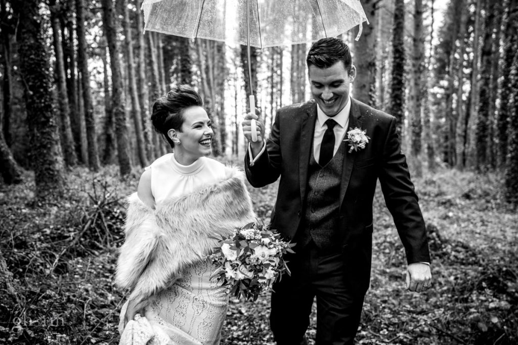 bride and groom walking through a forest as the rains pours down, bride and groom in donegal best wedding venue, harvey's point hotel on the shore of Lough Eske, Ghorm Studio Photography, donegal, sligo and leitrim wedding photographer
