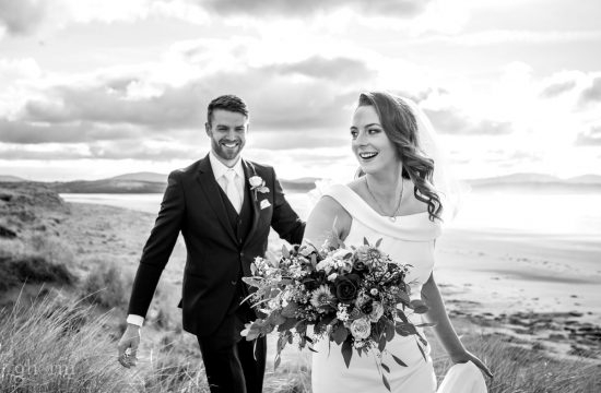 Bride and groom walking along the sand dunes on Dooey beach, lettermacward, co donegal. Photo by Paul McGinty ghorm studio photography.