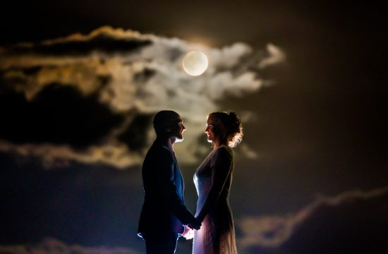 Bride and groom on the pier at Creevey Pier on their wedding night as the harvest moon shines behind them. Photo by Paul McGinty, Ghorm Studio Photography