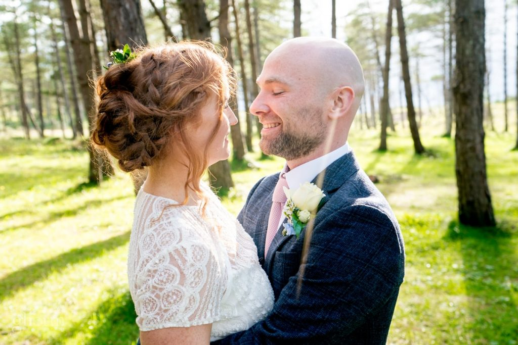 bride and groom embracing in a forest near the beach in Donegal as the sun sets. Creevet Pier hotel wedding, photos by Paul McGinty from Ghorm Studio Photography.
