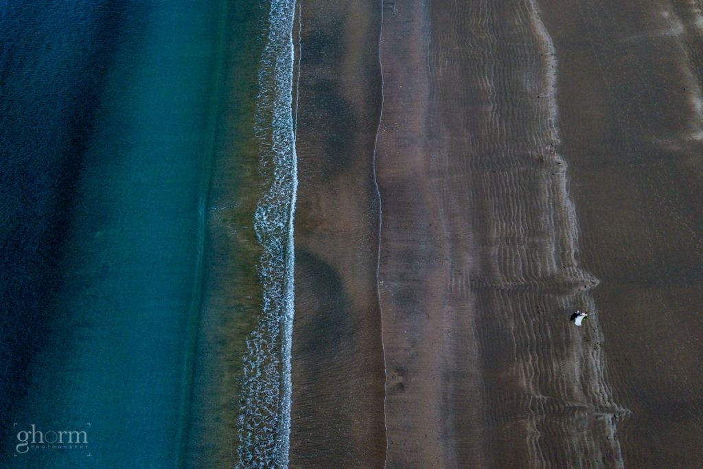 bride and groom walking on the beach in Donegal Murvagh, with a drone, Creevet Pier hotel wedding, photos by Paul McGinty from Ghorm Studio Photography.