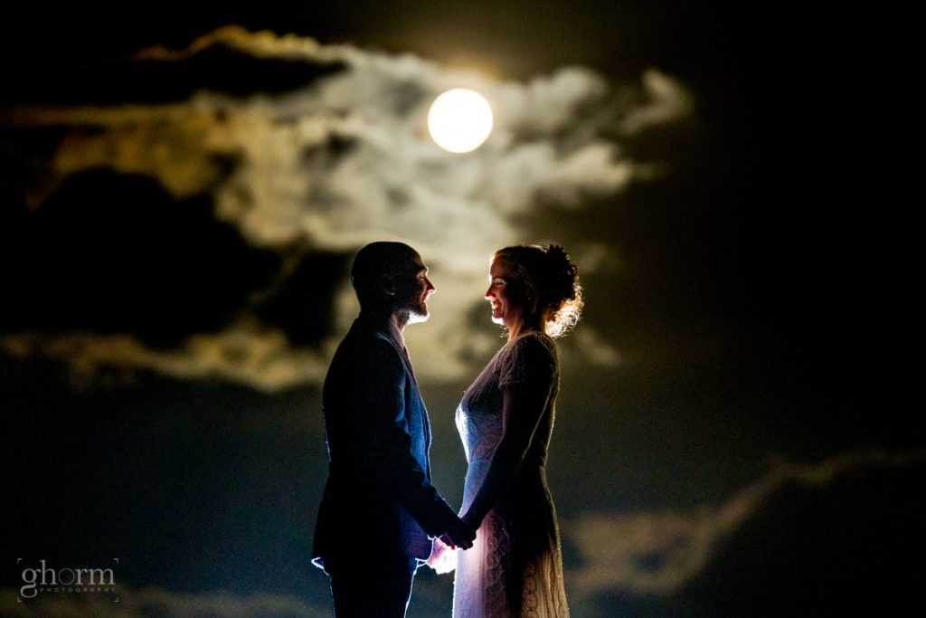 bride and from outside their wedding venue with the harvest moon behind them.Creevet Pier hotel wedding, photos by Paul McGinty from Ghorm Studio Photography.